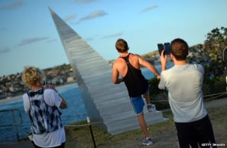 A man poses before a sculpture of stairs that lead into the sky