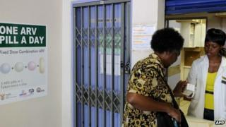 A woman receives medication at a pharmacy north of Johannesburg, South Africa