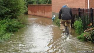 Man riding bike in flooded street in Haydon Wick