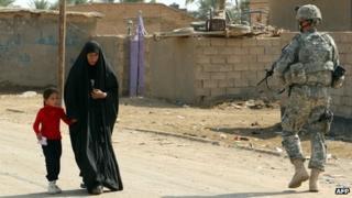 An Iraqi woman walks past a US soldier near a school in the town of Iskandiriyah, Iraq on 27 October 2011