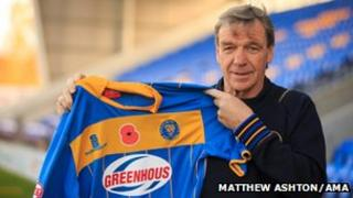 Shrewsbury Town manager Graham Turner holding a poppy shirt