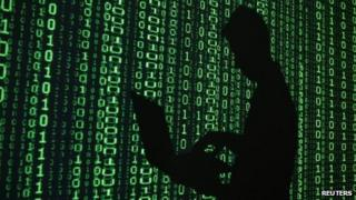 Man with laptop in front of binary code projection (file photo)