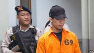 Separiano (right) being escorted by police before his trial in Jakarta