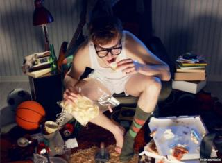 An image of a male student in a very messy room