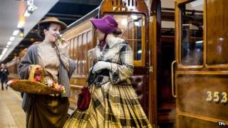Women in heritage costumes next to the carriage