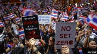 People wave flags and hold placards as thousands protest against the amnesty bill in Bangkok's central business district, Thailand, 6 November 2013