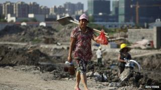 A female migrant construction worker walks towards her dormitory after a shift at a residential construction site in Shanghai on 6 August 2013