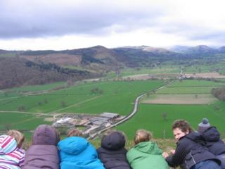 Children look over towards the Llwyn Bryn Dinas Hillfort in Powys