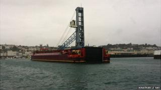 Mobile crane on barge entering Guernsey's St Peter Port Harbour