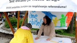 A Croatian woman signs a petition calling for a referendum to introduce a constitutional clause defining marriage as a union between a man and a woman.