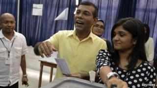 Maldivian Democratic Party (MDP) presidential candidate Mohamed Nasheed, centre, casts his vote at a polling station during the presidential elections on 9 November 2013.