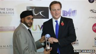 David Cameron receives his prize from Navdeep Singh, founder of the awards
