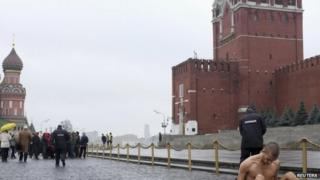 Performance artist Pyotr Pavlensky (bottom right) sits nailed to Red Square, 10 November