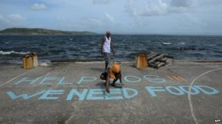 "A man paints a message reading ""Help SOS We Need Food"" at Anibong in Tacloban, eastern island of Leyte (11 November 2013)"