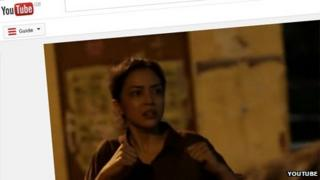 A still from the film, showing a woman with her fists clenched