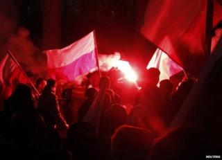 Rioters light flares outside the Russian embassy in Warsaw, 11 November