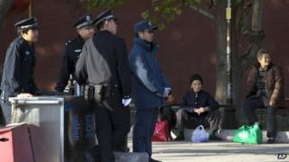 Elderly Chinese women sit on the sidewalk near a security checkpoint set up as part of the increased security during a weekend gathering of the Communist Party's 205-member Central Committee for its third annual plenum in Beijing Tuesday, Nov 12, 2013.