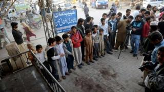 Pakistani youth and onlookers gather at the spot where Nasiruddin Haqqani, a senior leader of the feared militant Haqqani network, was assassinated outside the Afghan bakery in the Bhara Kahu area on the outskirts of Islamabad on November 11, 2013.