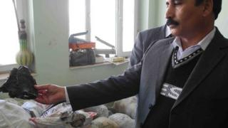 Colonel Fakhar Gul, head of Herat counter-narcotics police, with piece of raw opium in his hand