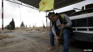 A female member of the Kurdish People's Protection Units (YPG) checks her weapon in Al-Rmelan, Qamshli province