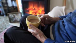 An old man sat by a fire