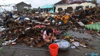 A girl pauses while washing clothes amongst the debris in an area devastated by Typhoon Haiyan