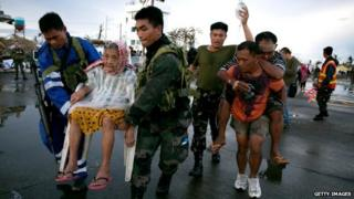 An elderly lady and an injured man are evacuated after Typhoon Haiyan