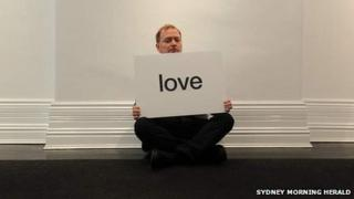 """Charles Frith holding printed word """"love"""""""