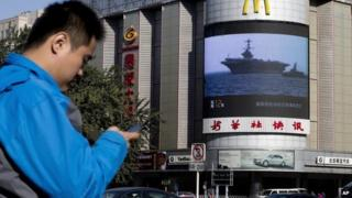 A Chinese man checks his mobile phone near a huge screen showing a news report of the deployment of US aircraft carrier USS George Washington to typhoon-hit Philippines on 14 November 2014