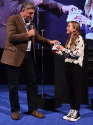 Agnieszka Kolaczynska receiving her award from actor Jim Carter