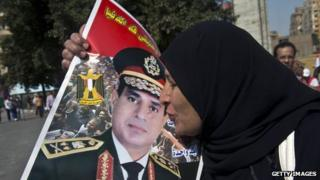 An Egyptian woman kisses a poster of Gen Abdul Fattah al-Sisi