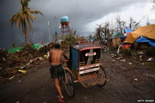 A man pushes a rickshaw through a demolished street in Leyte, Philippines