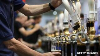 Barmen pull pints of beer