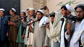 Taliban fighters carry their weapons prior to handing them over at a government peace and reconciliation ceremony in Jalalabad, capital of Nangarhar province on 27 October 2013.