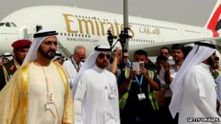 Ruler of Dubai Sheikh Mohammed Bin Rashid al-Maktoum (L) walks past an Emirates Airline's Airbus A380 as he attends the opening ceremony of the Dubai Airshow