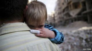 A man holds a child that he said survived shelling from forces loyal to President Bashar al-Assad, in Duma neighbourhood in Damascus, 17 November