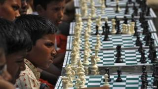 School children play chess in a public park in Chennai