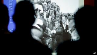 People watch a slideshow of President John F. Kennedy in Tampa, Florida on 18 November 2013