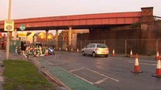 Cars by railway bridge