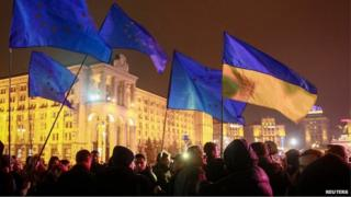 Protesters hold Ukrainian and European Union flags during a rally to support euro integration in central Kiev, 21 November 2013