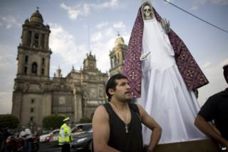 Man stands by statue of Santa Muerte in front of cathedral