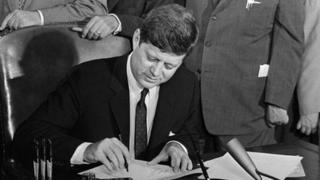 President John F Kennedy signs legislation at the White House on May 26, 1961.