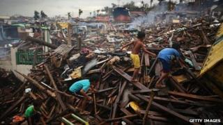Children climb through debris left from Typhoon Haiyan