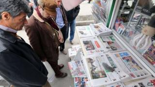 Iranians look at papers at a newsstand