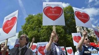 Demonstrators protesting against a gay marriage bill hold placards outside Parliament in June