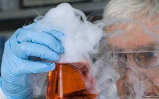 Scientist holds smoking beaker
