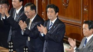Japanese PM Shinzo Abe (second from right) claps with lawmakers from his Liberal Democratic Party after the secrecy law was approved in parliament's lower house