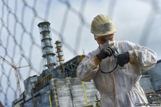 A man in white radiation protection gear in front of the nuclear reactor