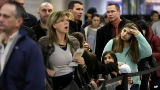 Travellers wait in line to board a flight at LaGuardia Airport in New York, on 26 November 2013