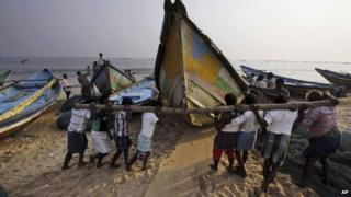 Indian fishermen move boats away from the coast following a cyclone warning in Orissa on 26 November 2013